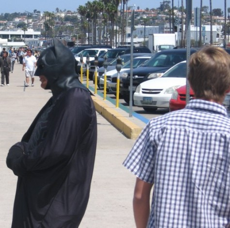 Batman shuns a young man who passes by.