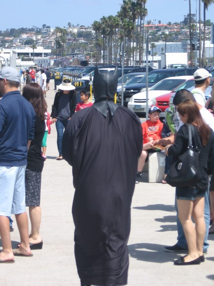 Citizens ignore sad Batman, who mopes and shuffles along.